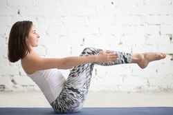 Young attractive woman practicing yoga, sitting in boat pose, navasana exercise, working out wearing sportswear, top, pants, indoor full length, white loft studio background