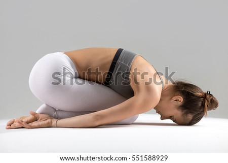 Young attractive woman practicing yoga, sitting in Child exercise, Balasana pose, working out wearing sportswear, white pants, bra, indoor full length, isolated against grey studio background