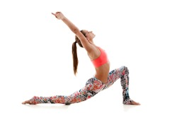 Young attractive woman practicing yoga, standing in anjaneyasana exercise, Horse rider pose, working out, wearing sportswear, red sport bra, pants, full length, isolated, white studio background