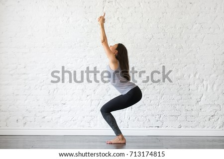 Young attractive woman practicing yoga, standing in Chair exercise, doing Utkatasana pose, working out, wearing sportswear, gray tank top, black pants, indoor full length, studio background