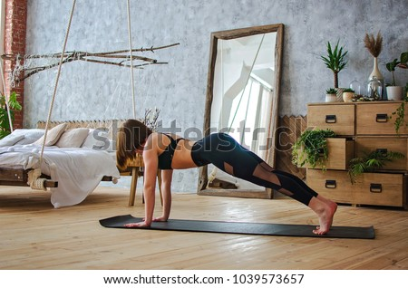 Young attractive woman practicing yoga, standing in chaturanga dandasana exercise, four limbed staff, Push ups or press ups pose