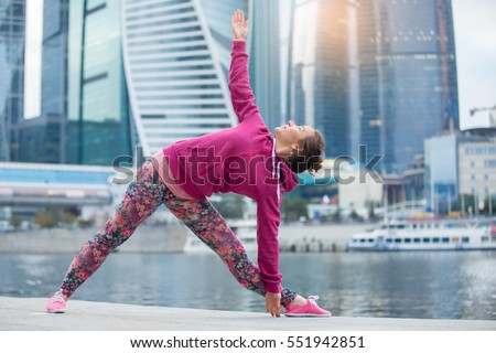Young attractive woman practicing yoga, standing in extended triangle exercise, Utthita Trikonasana pose, working out wearing pink sportswear, outdoor full length, modern skyscraper, river background