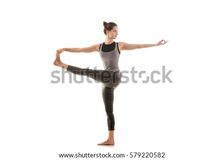 Young attractive woman practicing yoga, standing in Parivrtta Utthita Hasta Padangusthasana exercise, Twisting Extended Hand to Big Toe pose, working out, wearing sportswear, full length, isolated