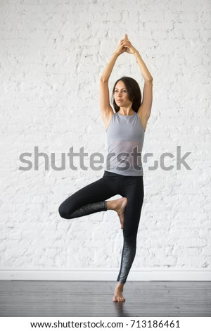 Young attractive woman practicing yoga, standing in Vrksasana exercise, Tree pose, working out, wearing sportswear, gray tank top, black pants, indoor full length, studio background