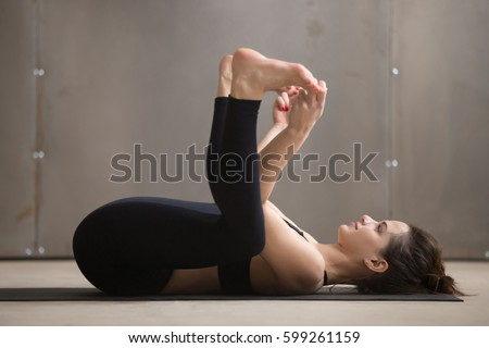 Young attractive woman practicing yoga, stretching in Ananda Balasana exercise, Happy Baby pose, working out, wearing black sportswear, cool urban style, full length, grey studio background, side view