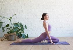 Young attractive woman practicing yoga, stretching in One Legged King Pigeon exercise, Eka Pada Raja Kapotasana pose, working out, wearing sportswear, cool urban style, full length, grey studio