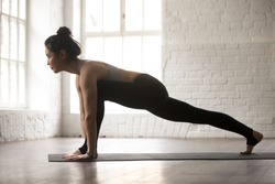 Young attractive woman practicing yoga, stretching in Utthan Pristhasana exercise, Lizard pose, working out wearing black sportswear bra and pants, full length, white loft studio background, side view