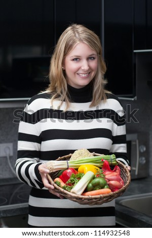 Young, attractive woman presents a basket with vegetables in the kitchen