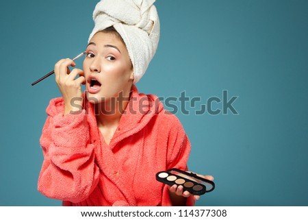 young attractive woman putting eye shadow with cosmetics brush over blue background, beauty treatment morning