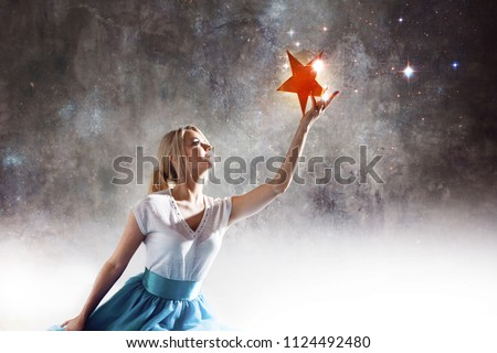 Young attractive woman reaching for the star. Take a star from the sky, dreams and plans, concept. Textured gray background #1124492480