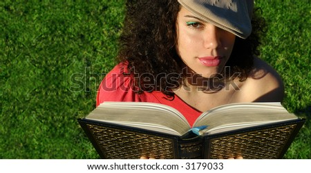 Young attractive woman reading a book as the sun sets.  Banner is usable as copy space or can be cropped down for a tighter shot.