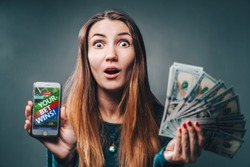 Young attractive woman showing sincere excitement about victory in online lottery. Girl being happy winning a bet in online sport gambling application on her mobile phone.