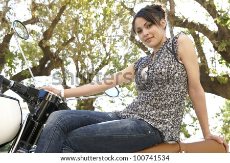 Young attractive woman sitting down on a motorbike with trees in the background, smiling at camera.