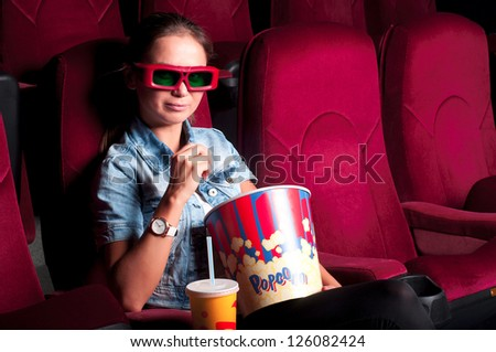 young attractive woman sitting in a cinema, enjoying a movie