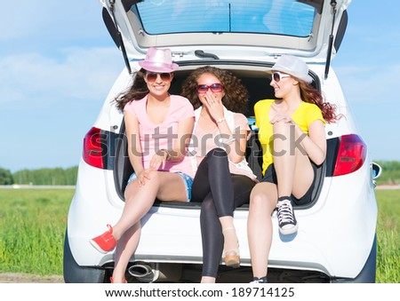 young attractive woman sitting in the open trunk of a new car, a summer road trip