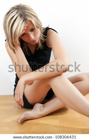 Young attractive woman sitting on floor - depressed and sad