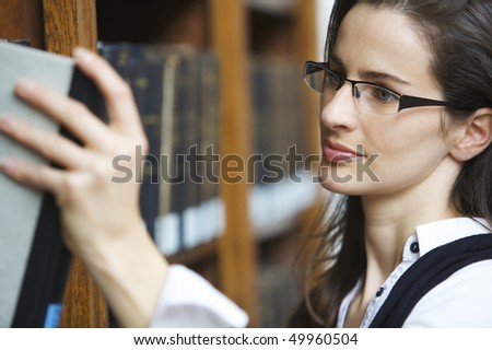 Young attractive woman standing at book shelf in old library pulling out a book. - stock photo