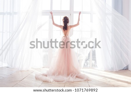 Young attractive woman standing by the window. Bride`s morning boudoir #1071769892