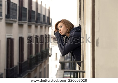 young attractive woman suffering depression and stress at the home balcony window terrace in pain and grief feeling sad and desperate in city urban background