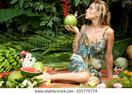 Young attractive woman surrounded by tropical fruits in an exotic garden.