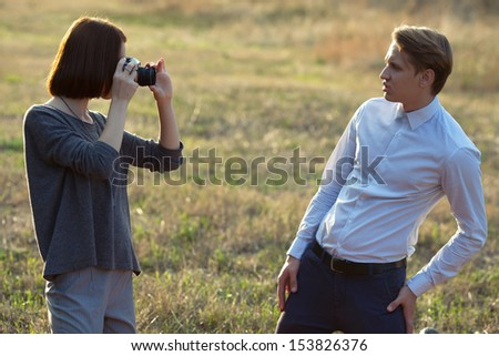 young attractive woman taking photos of her boyfriend in the park
