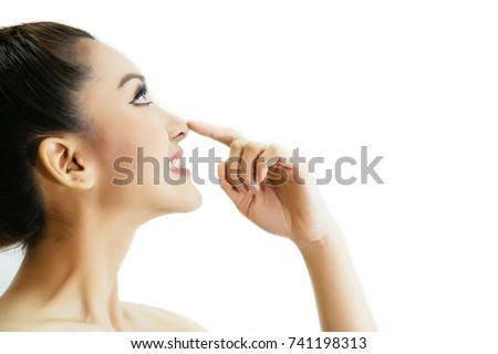 Young attractive woman touching her nose with fingertip over isolated white background