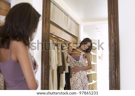 Young attractive woman trying on a dress in a fashion store, looking at her reflection in a mirror.