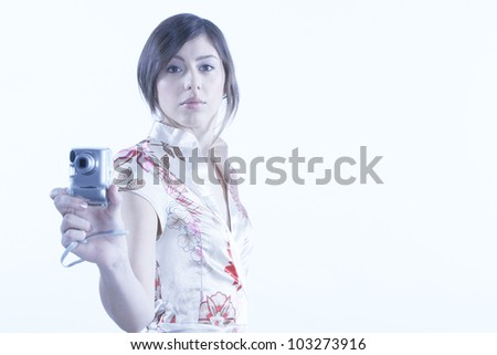 Young attractive woman using a digital photo camera on a plain background.