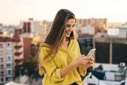 young attractive woman using her smartphone for send a message. female in a yellow blouse smiling on the rooftop while light is magic. Girl checking mobile phone. business woman watching at the screen