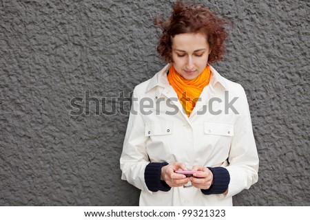 Young attractive woman using her smartphone outdoors - stock photo