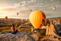 Young attractive woman watches and photographs flying colorful balloons on an early morning in Goreme Valley, Cappadocia. Turkey.Cappadocia one of the best places to fly with hot air balloons.