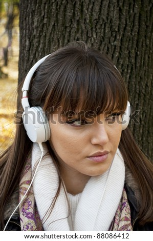 Young attractive woman with headphones listening music in park at fall outdoors