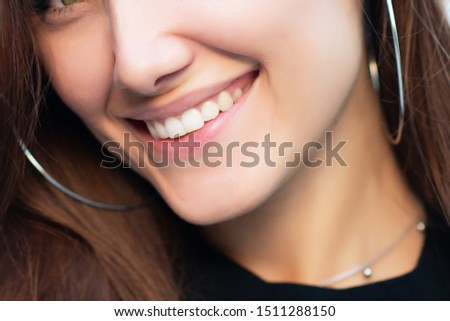 Young attractive woman with perfect smile winks at camera, summer outdoor portrait. Charming cheerful girl smiling and looking at camera. Beautiful female face.
