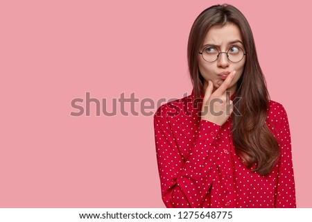 Photo of Young attractive woman with thoughtful expression, thinks about question, feels doubt, raises eyebrows, holds chin, dressed in formal clothes, isolated over pink background with free space on left