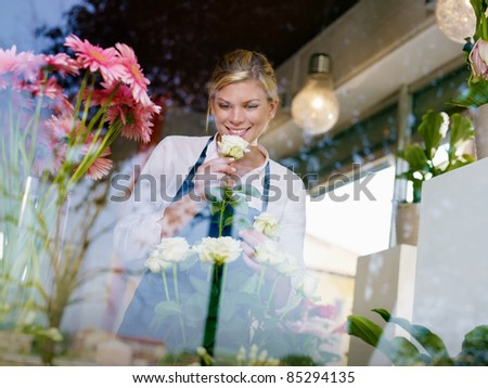 Young attractive woman working in flower shop, preparing bouquet and smelling white roses