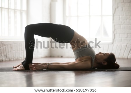Young attractive yogi woman practicing yoga concept, doing Glute Bridge exercise, dvi pada pithasana pose, working out, wearing black sportswear, full length silhouette on white loft studio background