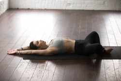 Young attractive yogi woman practicing yoga concept, lying in Reclined Butterfly exercise, supta baddha konasana pose, working out, wearing sportswear, full length, white loft studio background