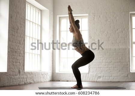 Young attractive yogi woman practicing yoga concept, standing in Utkatasana exercise, Chair pose, working out wearing sportswear, full length, white studio background, side view. Weight loss concept #608234786