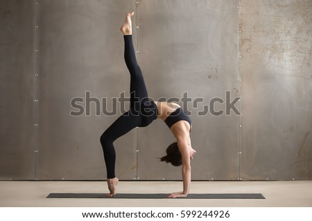Young attractive yogi woman practicing yoga, standing in Bridge exercise, One legged Wheel pose, working out, wearing black sportswear, cool urban style, full length, grey studio background, side view