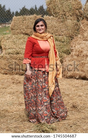 Young azeri woman in traditional Azerbaijani clothes, haystacks on background. Beautiful muslim woman, outdoors portrait