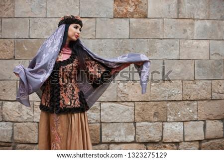 Young azeri woman in traditional Azerbaijani dress is dancing traditional azeri dance, outdoors. Novruz holiday celebration