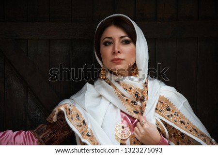 Young azeri woman in traditional Azerbaijani dress standing at the wooden door, outdoors. Novruz holiday celebration