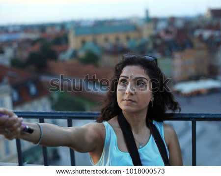 Young azeri woman making selfie on the top of the tower with the selfie-stick in  Warsaw, Poland