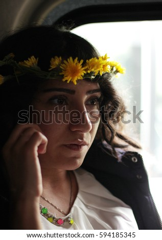 Young azeri woman with wreath at her head speaking the phone