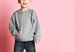 Young baby boy kid in grey hoodie and blue jeans with free text copy space happy smiling on pink background