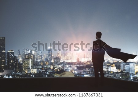 Young backlit super hero businessman on rooftop with night city view. Leadership and confidence concept