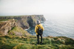 Young backpacker girl standing on the  Cliffs of Moher in yellow jacket with backpack