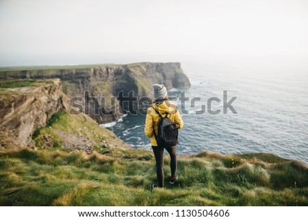 Young backpacker girl standing on the  Cliffs of Moher in yellow jacket with backpack Stock fotó ©