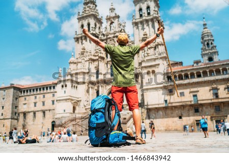 Young backpacker man pilgrim standing with raised arms on the Obradeiro square (plaza) - the main square in Santiago de Compostela as a end of his Camino de Santiago pilgrimage. Foto d'archivio ©