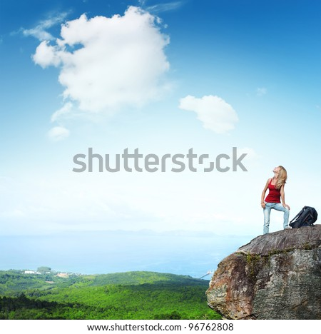Young backpacker standing on a cliff and enjoying a view